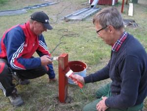 Lasse och Björn målar stolparna med röd färg